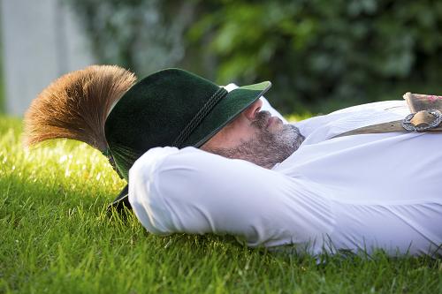 Schlafender Mann in Lederhose mit Hut auf der Wiesn